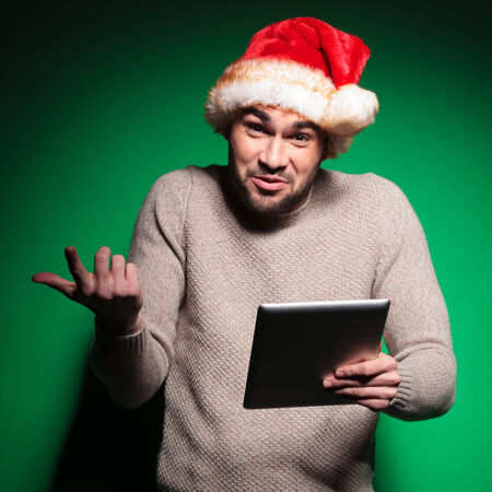 undecided young santa man holding a tablet pad computer on green background photo
