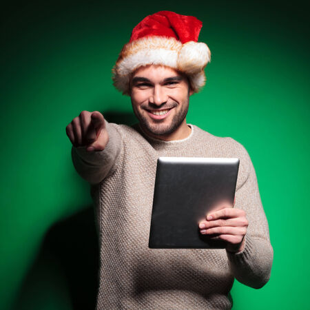 young santa man is pointing finger while reading on tablet pad computer photo