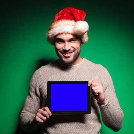 smiling young man wearing santa claus hat is showing you the blank screen of his tablet pad computer on green background photo
