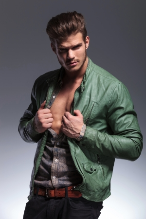 portrait of a fashion man pulling his shirt and jacket to reveal his muscular chest photo