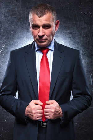 old man portrait: dramatic pose of a confident old business man pulling his suit and looking at the camera