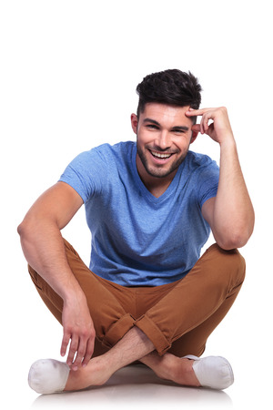 young pensive casual man sitting relaxed on white background photo