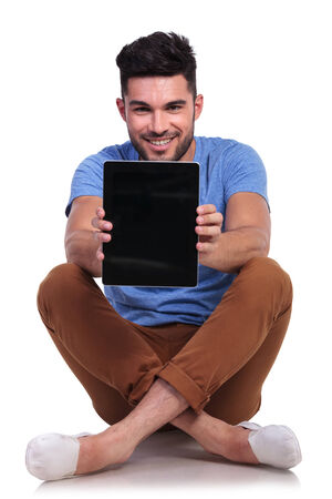 seated young man showing the blank screen of his tablet computer photo