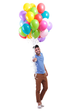 smiling casual man is offering a bunch of baloons on white background photo