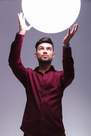 young casual man reaching out to a big ball of light on studio background photo