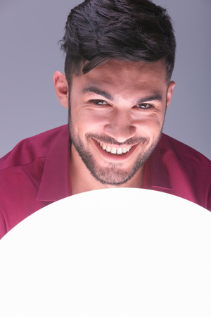 closeup picture of a young casual man smiling above a ball of light photo