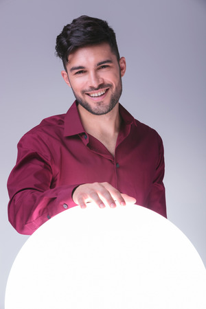 casual man holding his hand on a big sphere of light and smiles to the camera photo