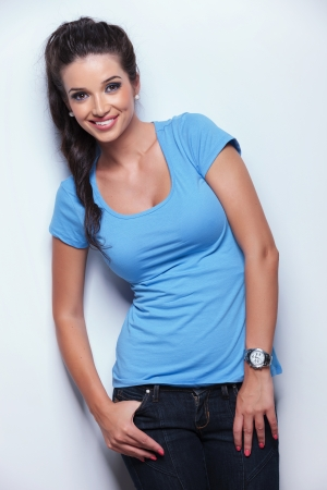 happy young casual woman posing for the camera, leaning a light gray wall photo