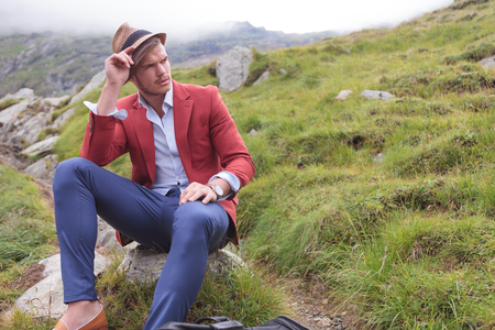 fashion young man wearing hat is sitting on rock and looking away photo
