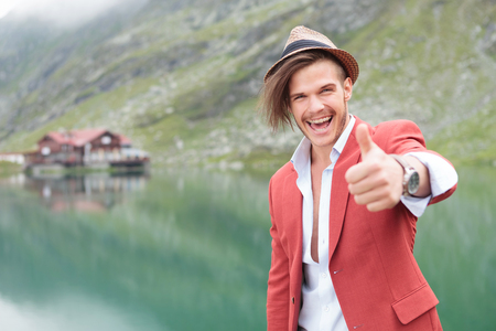 excited young casual man making the ok thumbs up hand gesture near a mountain lake with cabin photo