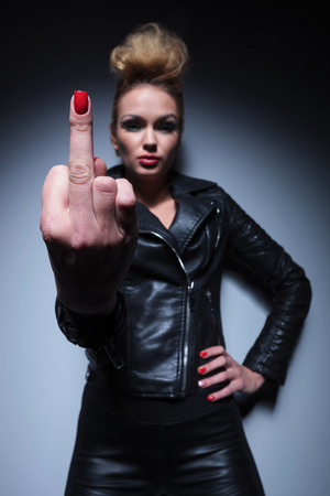 young fashion blonde woman giving you the finger on gray studio background photo