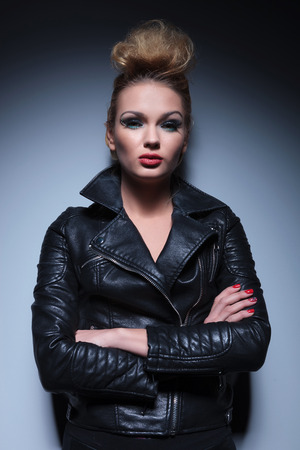 serious fashion woman in leather jacket standing with arms crossed against gray studio background photo