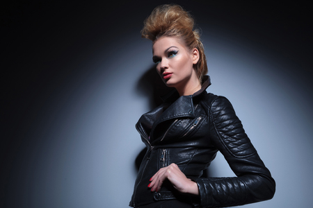 young beauty woman in leather clothes standing with hands on hips and looking away to her side photo