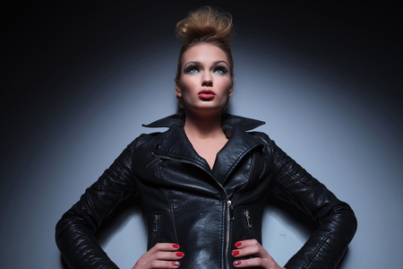young sexy blonde woman in leather jacket standing with hands on hips and looking up photo