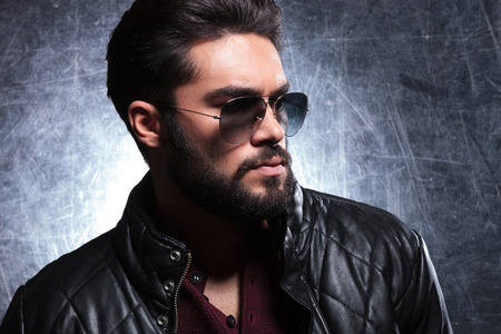side view of a young man with long beard in sunglasses, looking away fron the camera photo