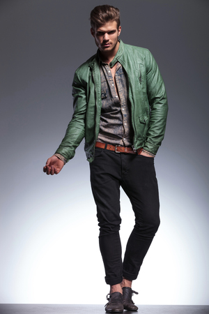 young casual man in leather jacket and jeans making a fashion pose for the camera photo
