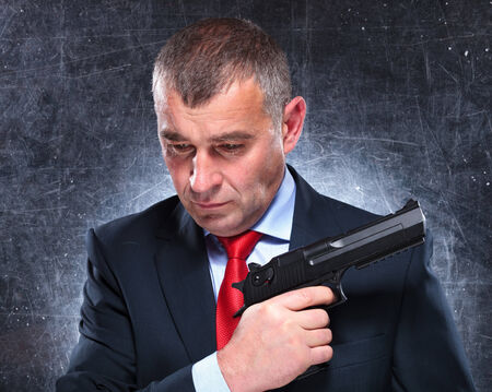 pensive old assassin holding his gun and looking away from the camera photo