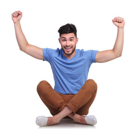 seated young man is winning with his hands in the air, on white background photo