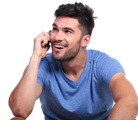 happy young man is talking on the phone and looks up to his side on white background photo