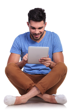 seated happy casual man working on his tablet pad computer photo