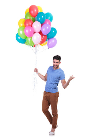 happy casual man holding a bunch of balloons is inviting to a party Stock Photo