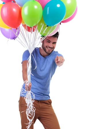 young casual man holding balloons and pointing to the camera
