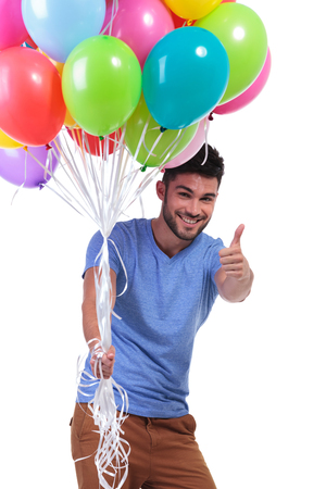 smiling casual man holding a bunch of balloons and making the ok thumbs up sign photo