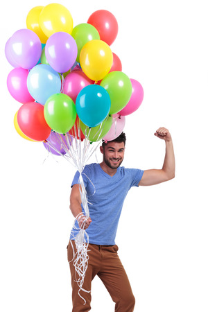 happy casual man winning a big bunch of balloons on white background