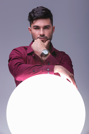 pensive young man standing with hands against a big ball of light photo