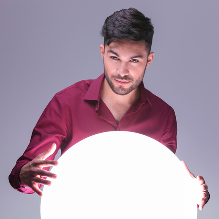 casual man acting as a fortune teller with his big ball of light photo