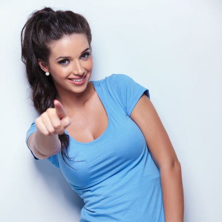 young casual woman smiling and pointing her finger to you photo