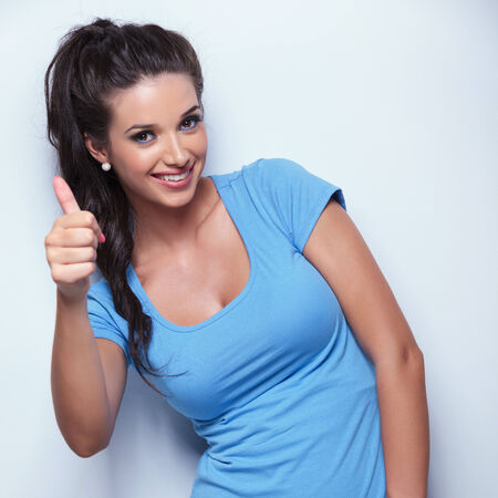 thumbs up gesture: happy young casual woman making the ok thumbs up hand sign , studio shot Stock Photo