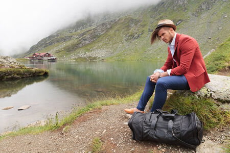young casual man is resting on a rock near a mountain lake with cabin photo