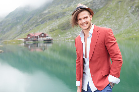 laughing young man standing near a lake in the mountains photo