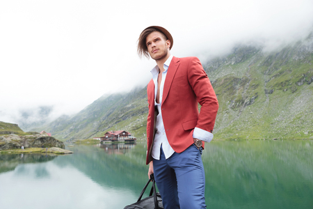 casual man with travel bag standing with hand in pocket and looks away, against a misty outdoor background with mountain lake with cabin photo