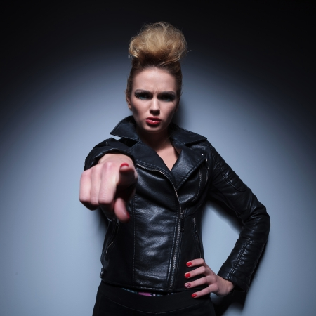 angry blonde: angry fashion woman in leather jacket is accusing you by pointing her finger Stock Photo