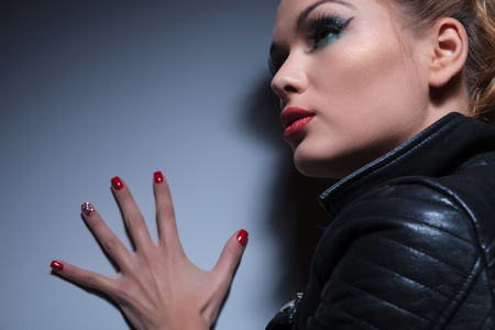 closeup picture of a woman with nice make up and red nails manicure, pushing the wall with a hand, wearing a leather jacket  photo