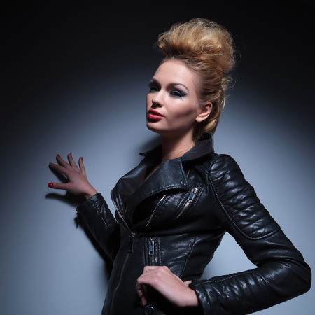 side view of a fashion woman in leather jacket leaning with one hand against a gray studio wall and looking away  photo