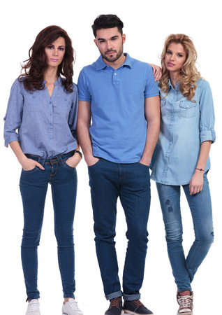 three young casual people standing and posing for the camera
