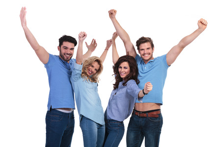 happy casual group of people celebrating victory with hands in the air on white background