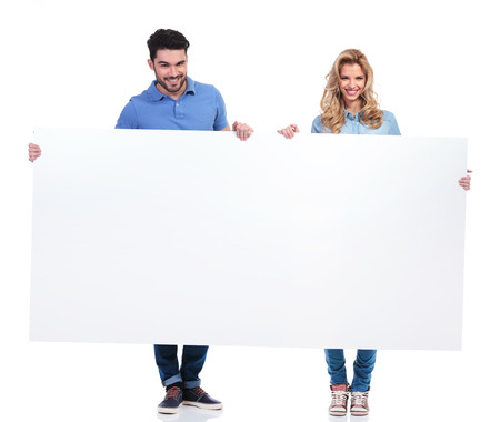 man holding sign: couple of casual people presenting a big blank billboard on white background