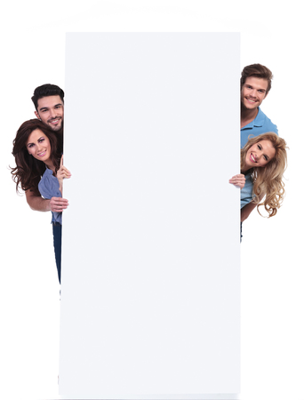 small group of people: four casual happy people hiding behing a big blank billboard on white background Stock Photo