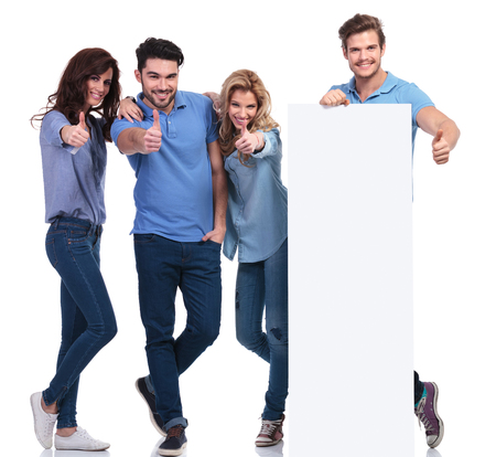 group of casual friends presenting a blank board and making the ok thumbs up hand sign on white background photo