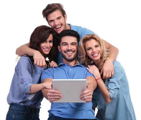 four laughing casual people reading on a tablet pad computer on white background photo