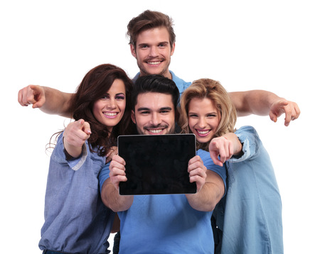 young group of people showing you the blank screen of a tablet pad computer and point fingers to the camera photo