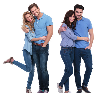 embraced: two happy couples of young casual people standing embraced on white background