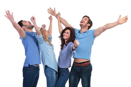 Grupo emocionado de gente ocasional jóvenes que celebraban el éxito y mirando hacia arriba con las manos en el aire Foto de archivo