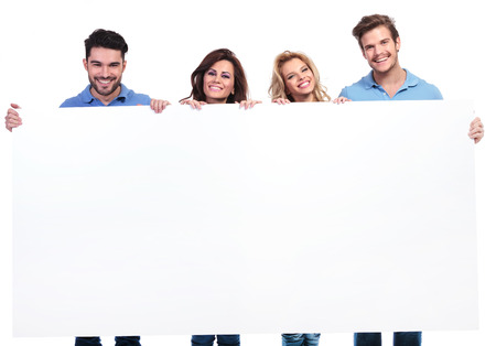 four young casual young people showing a big blank banner and smile on white background photo