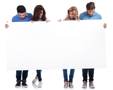 full body picture of casual people holding and looking at a blank board on white background photo