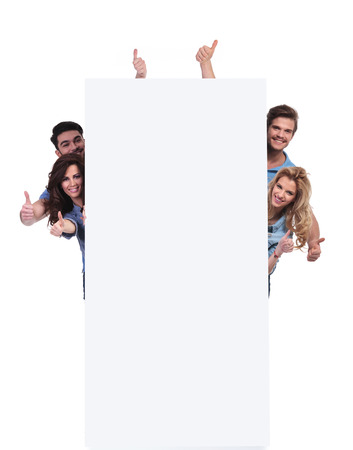 smiling casual people behind a big banner making the ok thumbs up sign onwhite background photo